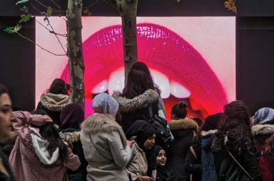 Mund mit roten Lippen auf Großbildschirm mit Zuschauern